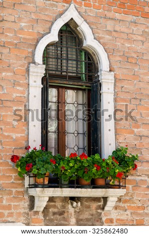 A lancet window with red geranium  in crocks in Venice - stock photo