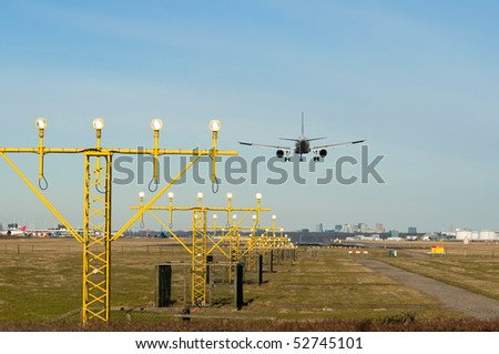 a landing airplane with landing-lights - stock photo