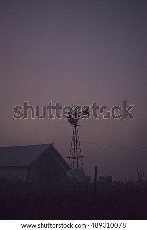 A landscape photograph of an old wind mill in the middle of a countryside farm. A foggy sunrise sets in the background.