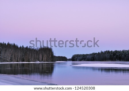 A landscape with winter river partially covered with ice in twillight - stock photo
