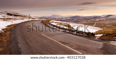 A 2-lane road winds across the snow-covered moors on Buttertubs Pass near Hawes in England's Yorkshire Dales National Park. - stock photo