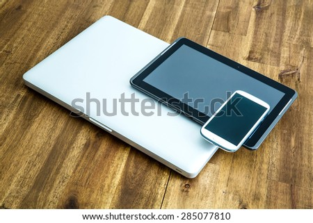 A Laptop computer, a Tablet PC and a Smartphone on a wooden Desktop.  - stock photo