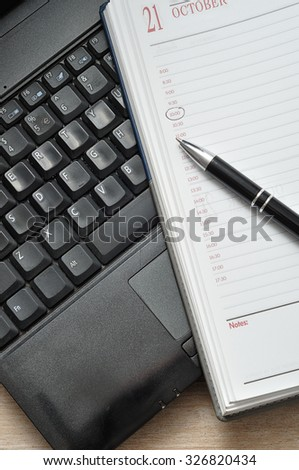 A laptop with an open diary and a pen - stock photo