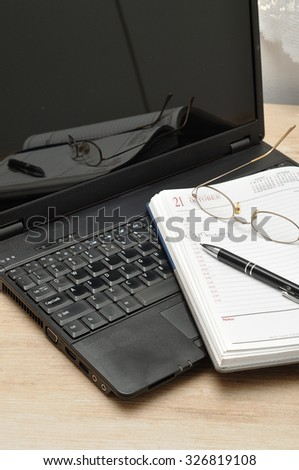 A laptop with reading glasses, a pen and an open diary  - stock photo