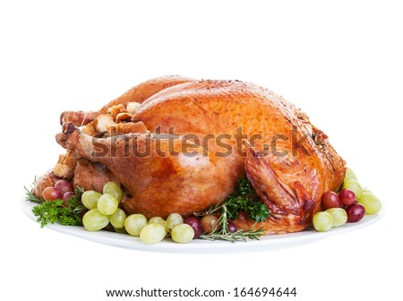 A large a stuffed turkey on a platter garnished with grapes.  - stock photo