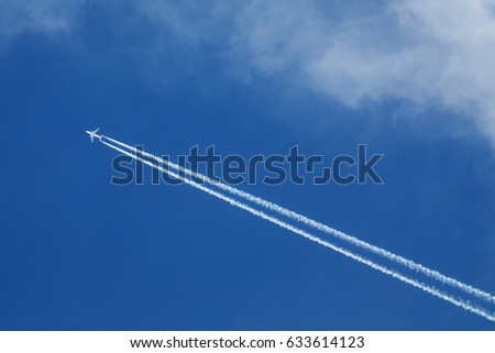 A large airliner flies high and creates white traces in the blue sky.