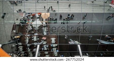 A large array of mirrors above the entrance doors to a popular shopping mall, reflect the people as they go about their day in Barcelona, on the coast of Spain. - stock photo