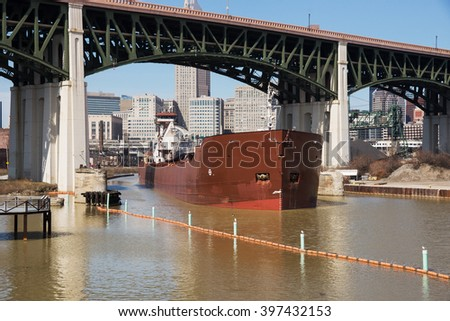 A large articulated tugboat and barge transporting taconite pellets to a local steel mill sails under the Hope Memorial Bridge upbound on the Cuyahoga River in Cleveland, Ohio