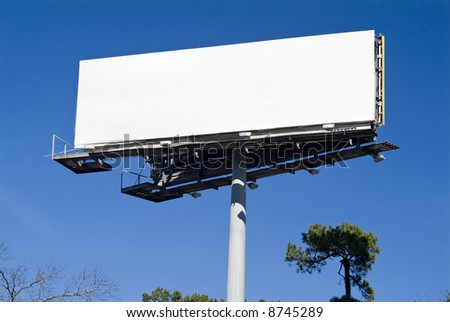 A large blank billboard taken against a bright blue sky. - stock photo
