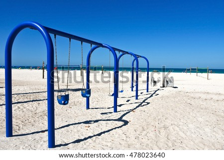 A Large Blue Metal Swing Set on a Sandy Beach