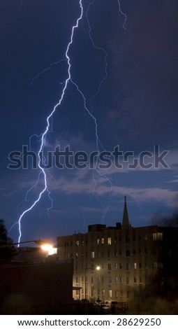 A Large bolt of lightning is caught near sunset across the blue sky over Washington DC. - stock photo