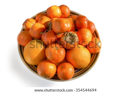 A large bowl full of citrus fruits and persimmons photographed against a white background - stock photo