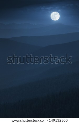 A large, bright moon rises over endless mountain ridges of deeply layered mountain forests in a rich blue tone late night tonality, while a misty fog settles in to the valleys. - stock photo