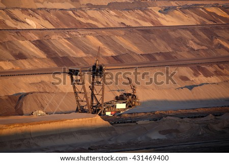 A large bucket wheel excavator digging lignite (brown-coal) in an open cast mine at sunset, Germany - stock photo
