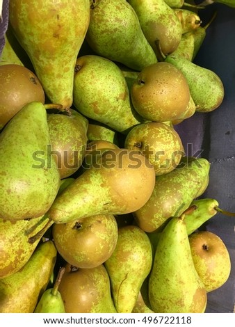 A large bulk bin of pairs at a fresh produce stand, juicy organic sweet green yellow pears background.