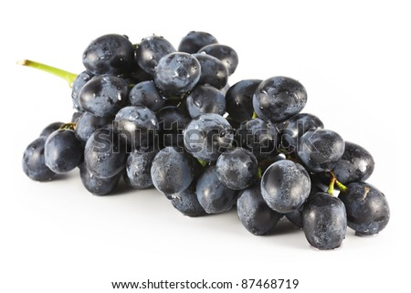 A large bunch of black grapes with drops of water on a white background. - stock photo