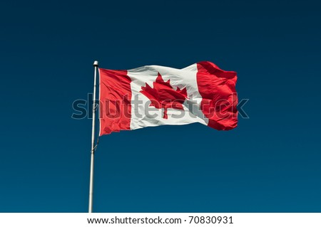 A large Canadian flag waves in the breeze in front of a deep blue sky.