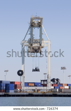 A large cargo crane is poised to unload another container ship.