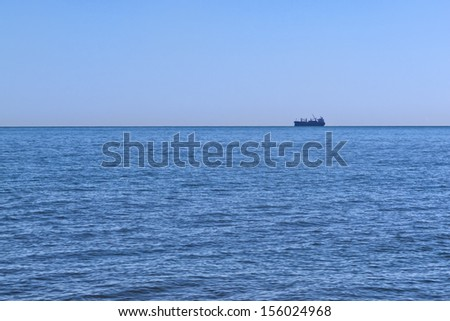 A large Cargo Ship on the Horizon, beautiful blue sea in front