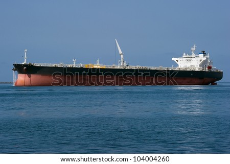 A large chemical tanker ship prepares to leave a harbor - stock photo