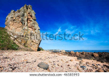 A large coastal rock formation along the Fife coastal trail near to St Andrews, Scotland. Photo taken on a bright spring morning, with deep blue sky in the background. - stock photo