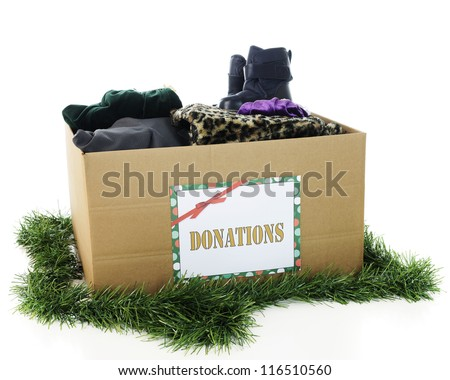 "A large corrugated box with a holiday ""Donation"" sign.  The box is filled with assorted winter clothing and surrounded by Christmas garland.  On a white background."