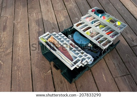 A large fishermans tackle box fully stocked with lures and gear for fishing. - stock photo