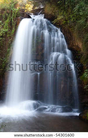 A large forest waterfall photographed with a slow shutter speed to create soft streaks of white water falling - stock photo