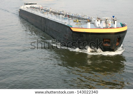 A large fuel cargo ship in a river. - stock photo