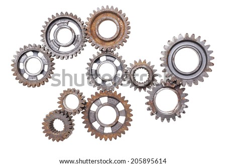 A large group of rusty transmission gears linked together on a white background.