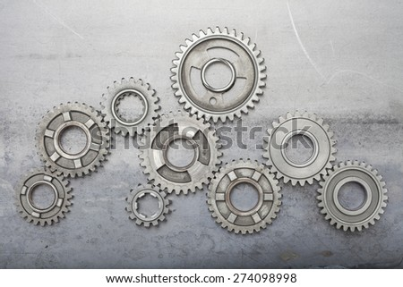 A large group of steel gears are linked together on top of a grungy metal background - stock photo