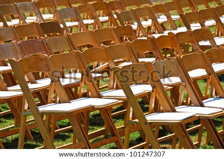 A large group of wooden chairs on lawn