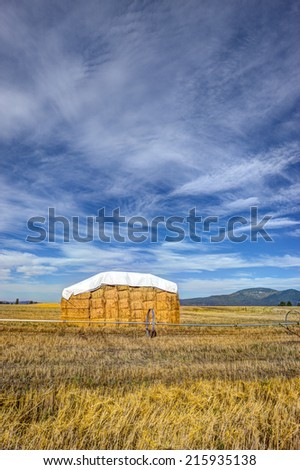 A large haystack in the Rathdrum Prairie under a rich partly cloudy blue sky in North Idaho.