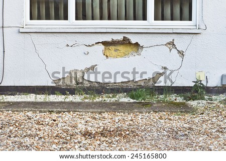 A large hole and cracks in a house wall - stock photo