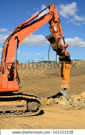 A large hydraulic rock breaker ram hammer installed on a track hoe excavator being used to break up stones at a new commercial construction development project - stock photo