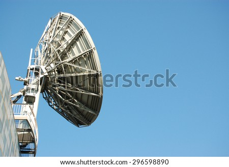 A large, industrial satellite dish used in the communications industry against a blue sky on a sunny, summer day with space for copy. - stock photo