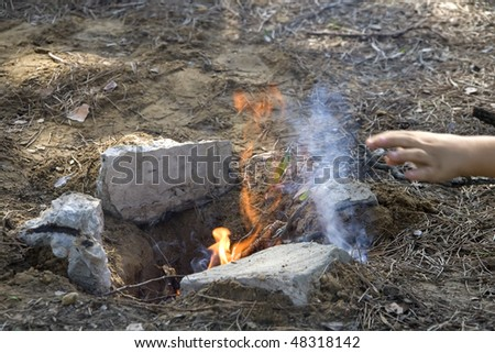 a large man adding fuel to the fire for a barbecue