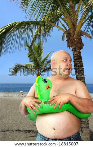 A large man with inflatable toy gets ready to go into the ocean.