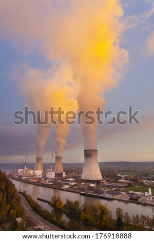 A large nuclear power station by a river during sunset