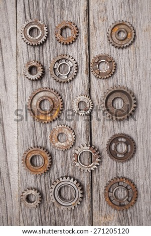 A large number of rusty metal gears sitting on some aged wooden planks. - stock photo