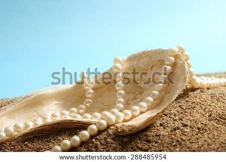 A large oyster shell and a pearl necklace on display over some sand. - stock photo