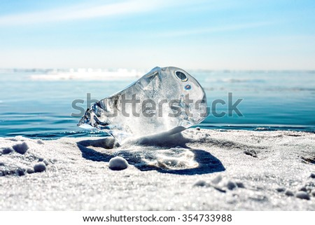 A large piece of ice on the surface of the transparent frozen Lake Baikal. Horizon. Blue transparent ice. floe. Lying on the ice.  Ice on Lake Baikal.  - stock photo