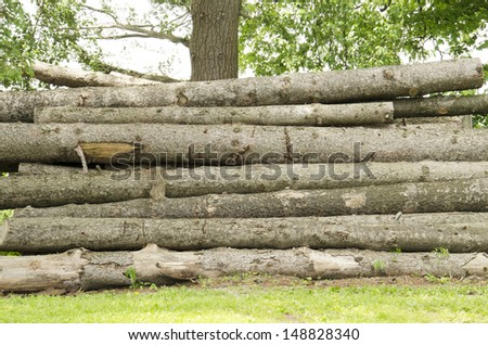 A large pile of logs stacked in a field - stock photo