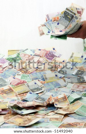 A large quantity of bank notes. A hand holding a part of the money - stock photo