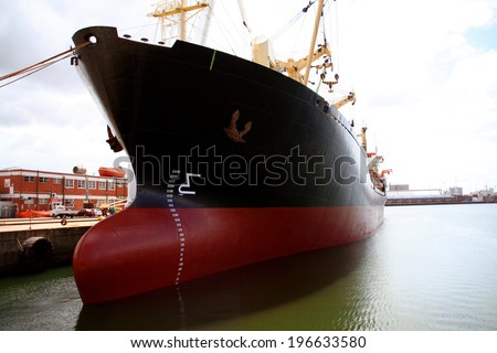 A large red and black tanker ship being renovated in a shipyard - stock photo