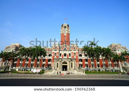 A large red brick tower overlooking the remaining building under a blue sunny sky. - stock photo