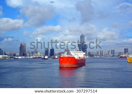 A large red oil tanker leaves Kaohsiung Port, in the background the skyline of the city.