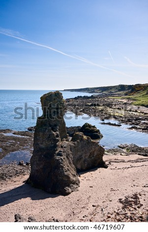 A large rock formation on a beach along the Fife coastal in Scotland. Bright morning light, with blue sky overhead. - stock photo