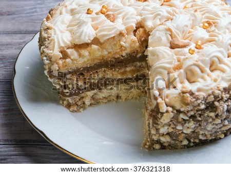 A large round air meringue cake torte with chocolate layer on a white porcelain dish on a wooden light background - stock photo