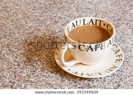 A large round cup of white coffee on a matching saucer. - stock photo